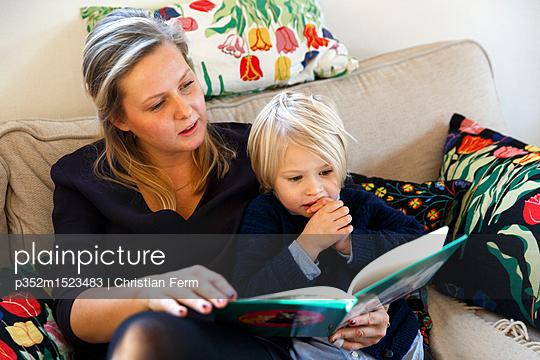 plainpicture | Photo library for authentic images - plainpicture p352m1523483 - A mother reading a book to ... - plainpicture/Folio Images/Christian Ferm