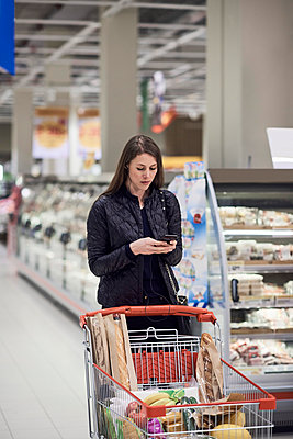 Woman text messaging while standing by shopping cart with groceries at supermarket - p426m1451852 by Maskot