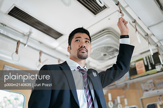 Young businessman on a train - p300m2140635 by Juri Pozzi