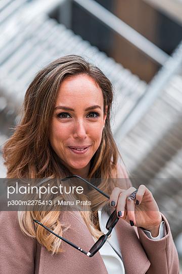 Beautiful female entrepreneur holding sunglasses - p300m2275413 by Manu Prats