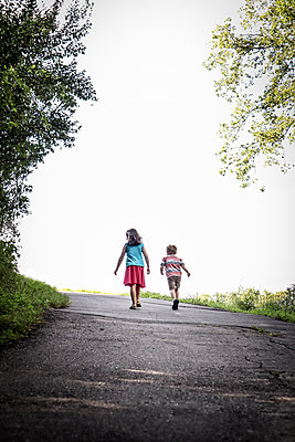 Siblings walk on country road - p1019m2122607 by Stephen Carroll