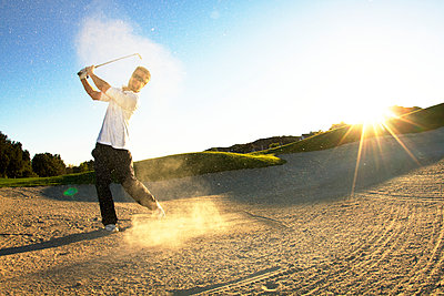 Man hitting golf ball while standing on field - p1166m969814f by Cavan Images