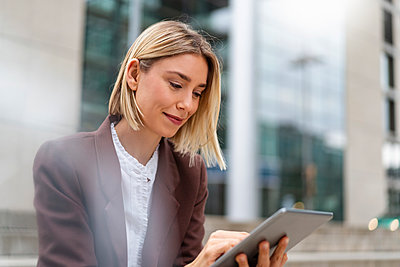 Young businesswoman using tablet in the city - p300m2143625 by Daniel Ingold