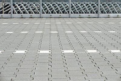 Pavement of a parking place with shopping carts in the background - p300m884895 by visual2020vision