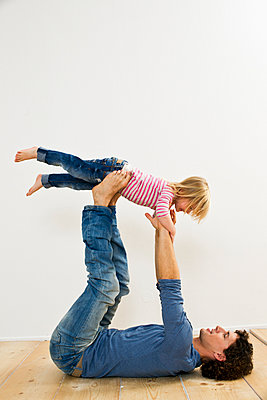 Studio shot of father lifting up daughter whilst lying on back - p429m895465f by Emely