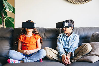 Mixed race children using virtual reality goggles on sofa - p555m1305900 by Inti St Clair photography