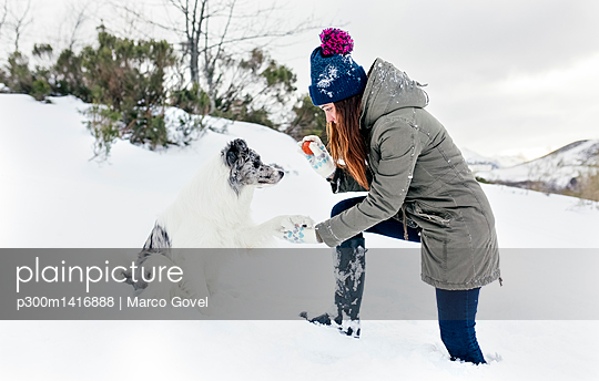 Young woman playing with her border collie in the snow - p300m1416888 by Marco Govel