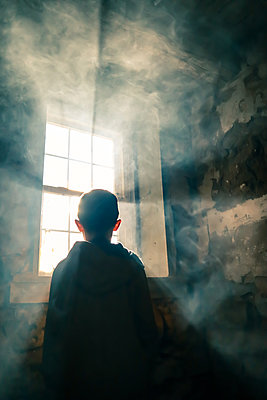 Boy at window in the glaring light - p1019m2128482 by Stephen Carroll