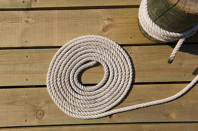 Circle of rope attached on a wood paneled surface - p1025m780058f by Björn Andrén