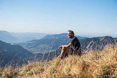 Junger Wanderer macht Pause vor Bergkulisse - p1142m2056575 von Runar Lind