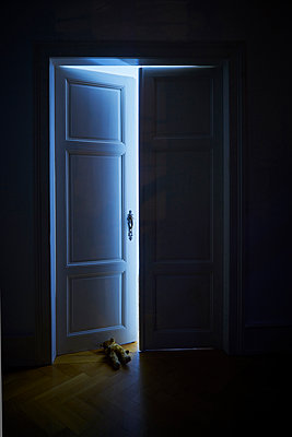 Apartment door at night with teddy bear on floor - p1312m2168096 by Axel Killian
