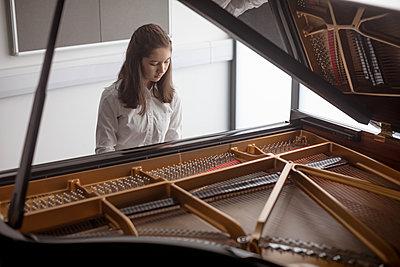 Adorable schoolgirl playing piano in music school - p1315m2003046 by Wavebreak