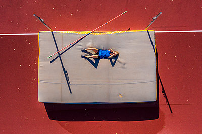 Germany, Baden-Wurttemberg, Winterbach, Female athlete lying on mat after failed high jump - p300m2155803 by Stefan Schurr