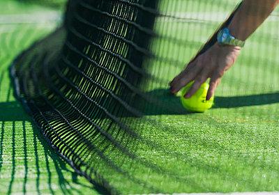 Retrieving a tennis ball by the net; tarifa cadiz andalusia spain - p442m700122f by Ben Welsh