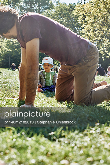 Father and baby boy playing in the meadow, Social distancing due to Covid-19 - p1146m2182019 by Stephanie Uhlenbrock