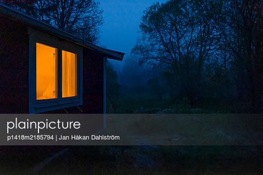 Illuminated cottage window - p1418m2185794 by Jan Håkan Dahlström