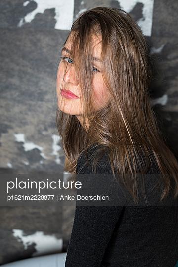 Girl in front of cow skin wallpaper - p1621m2228877 by Anke Doerschlen