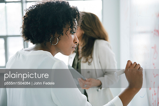 Businesswoman writing on whiteboard in meeting - p555m1504084 by John Fedele