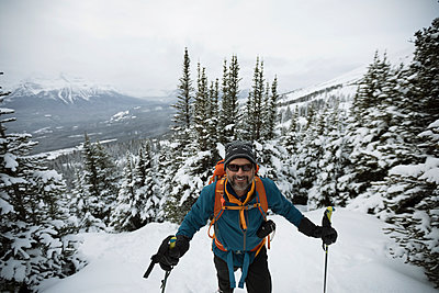Portrait confident senior man snowshoeing, climbing snowy mountain hill - p1192m1546527 by Hero Images