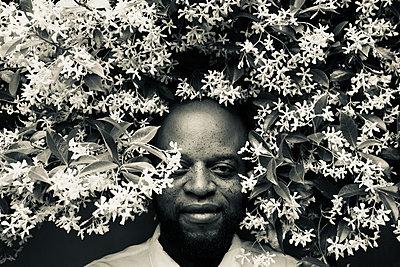 Dark-skinned man between flowers - p1640m2245848 by Holly & John