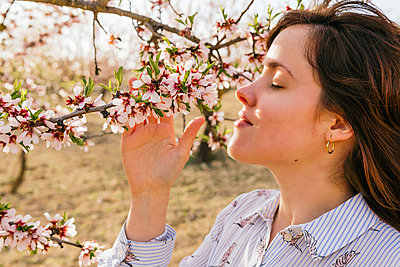 Beautiful woman smelling blossom of almond tree - p300m2276774 by Mar