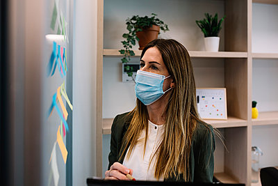 Concentrated businesswoman with protective face mask working at office - p300m2277752 by Xavier Lorenzo