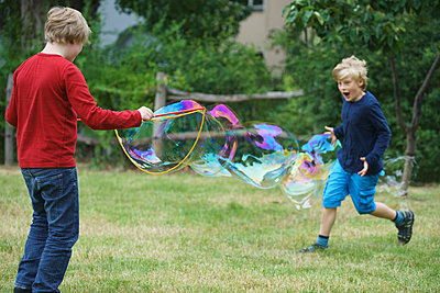 Happy brothers playing with soap bubble in back yard - p301m1180565 by Halfdark
