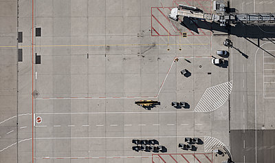 View from above airport service vehicles and passenger boarding bridge on tarmac at airport - p301m2016355 by Stephan Zirwes