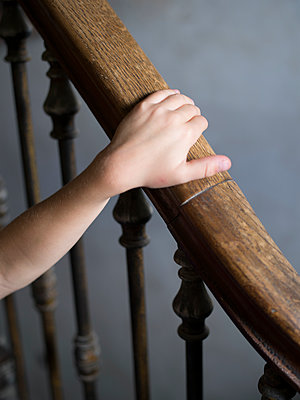 Child's hand on handrail - p945m1467740 by aurelia frey