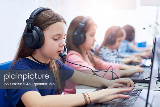 Pupils wearing headsets and using laptops in school - p300m1587245 von gpointstudio