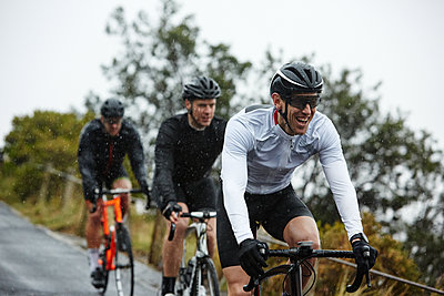 Smiling male cyclist cycling with friends - p1023m1584017 by Richard Johnson