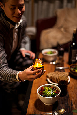 queer person smiles and places candle at dinner table at night - p1166m2258401 by Cavan Images