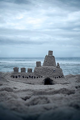 Sandcastle on beach on gloomy day  - p1248m2172155 by miguel sobreira