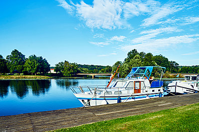 Boat on a jetty on the canal - p1312m2103830 by Axel Killian