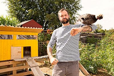 Portrait of man with Polish chicken at chickenhouse in garden - p300m2083647 by Michelle Fraikin