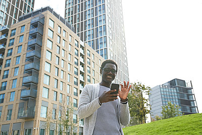 Smiling male entrepreneur using mobile phone while standing against office building in downtown - p300m2241043 von Pete Muller