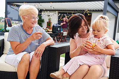 Senior and mature women with female toddler on lap at family lunch on patio - p429m1494226 by Gpointstudio
