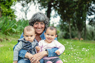 Grandmother with two grandchildren on lap in garden, Florence, Italy - p429m2165135 by Innocenti