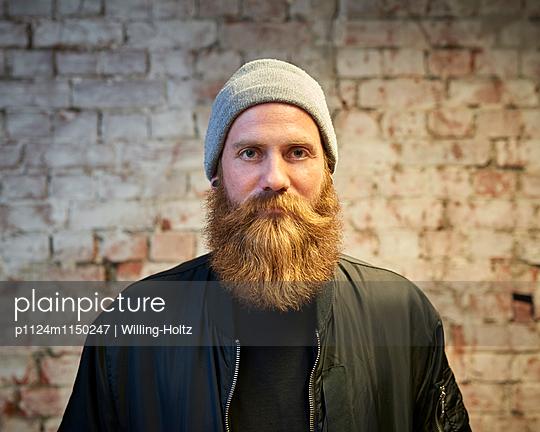 Mann mit Bart und Mütze vor einer Steinmauer - p1124m1150247 von Willing-Holtz