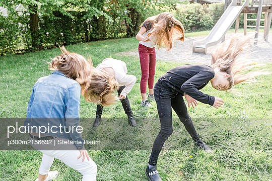 Four girls shaking their heads covered with dandelion seeds - p300m2156692 by Stefanie Baum