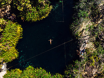 From above female with outstretched arms enjoying bath in clean Cenote - p1166m2137546 by Cavan Images