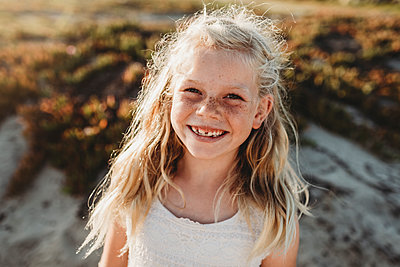 Portrait of young school age girl with freckles smiling at camera - p1166m2165872 by Cavan Images