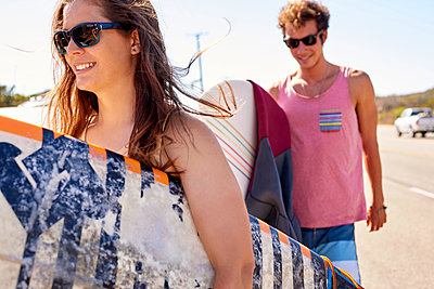 Smiling young couple carrying surfboards on coastal road - p300m1206225 by Fotoagentur