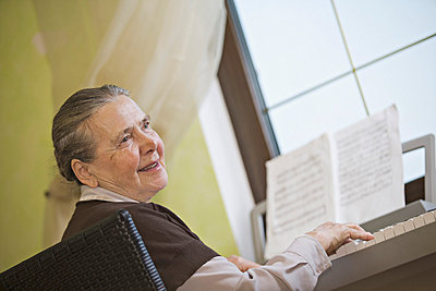 A cheerful senior woman playing an upright piano - p301m731174f by Vladimir Godnik
