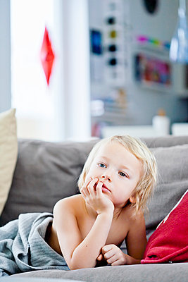 Young blond child relaxing on couch - p312m1551951 by Johner Images