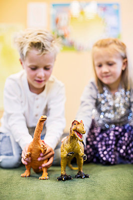 Children playing with toy dinosaurs in kindergarten - p426m920164f by Maskot