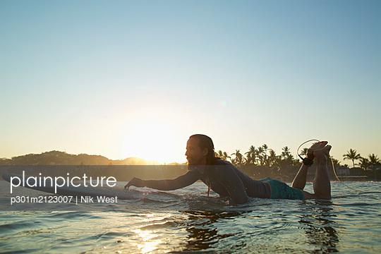 Male surfer paddling out on sunset ocean, Sayulita, Nayarit, Mexico - p301m2123007 by Nik West
