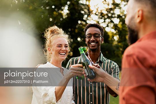 Happy friends having beer in garden - p312m2237310 by Plattform