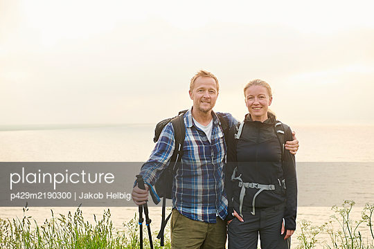 Two hikers, man and woman, embracing on a coastal path - p429m2190300 by Jakob Helbig