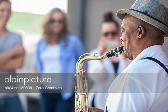 Street musician, playing saxophone, entertaining pedestrians - p924m1139309 by Zero Creatives